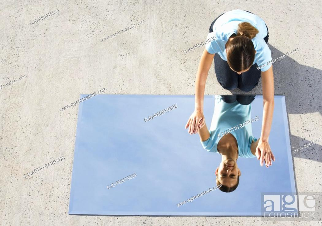 Stock Photo: Woman kneeling on ground with mirror and reflection.