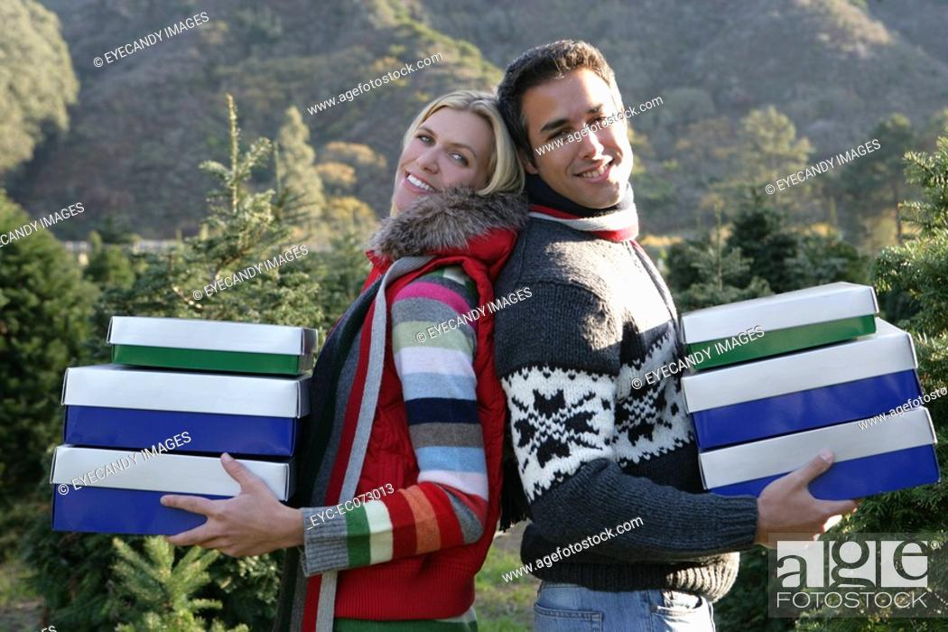 Stock Photo: Young couple holding Christmas boxes.