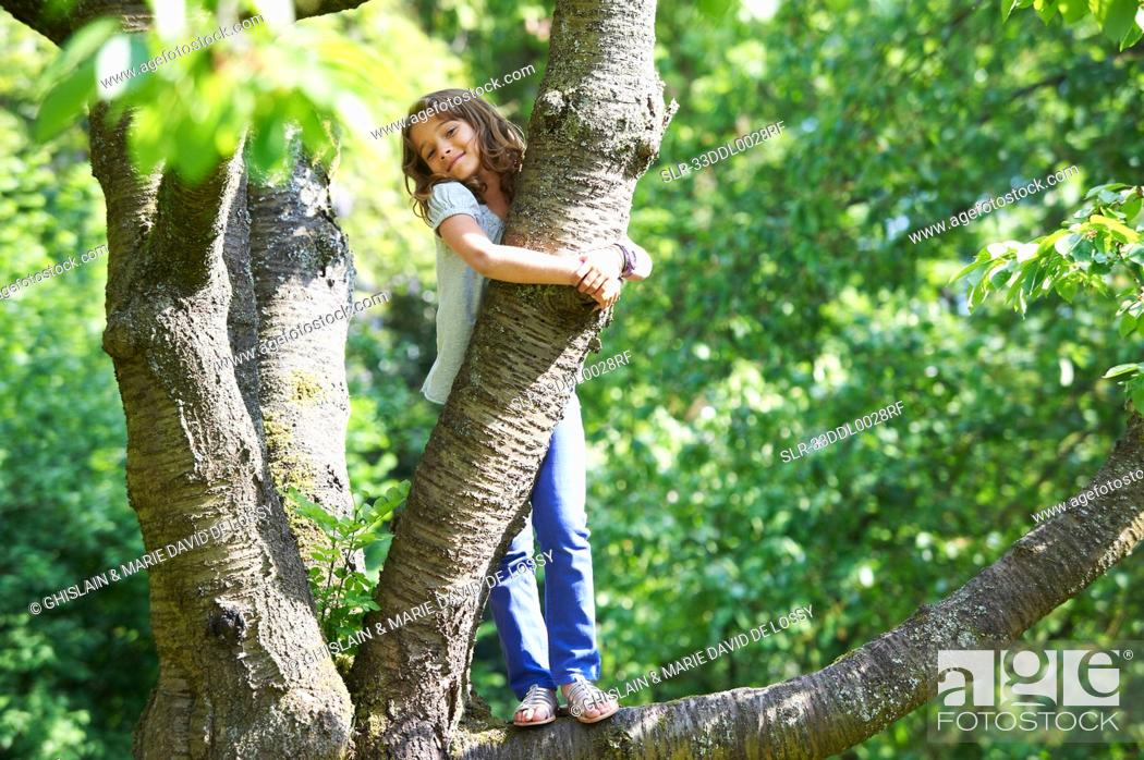 Stock Photo: Smiling girl climbing tree outdoors.