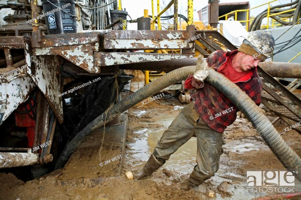 Stock Photo: Mancelona, Michigan - A worker struggles with a hose while dismantling a natural gas drilling rig in the Antrim Shale field of northern Michigan.