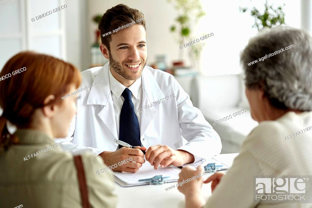 Stock Photo: Smiling doctor talking with senior patient.
