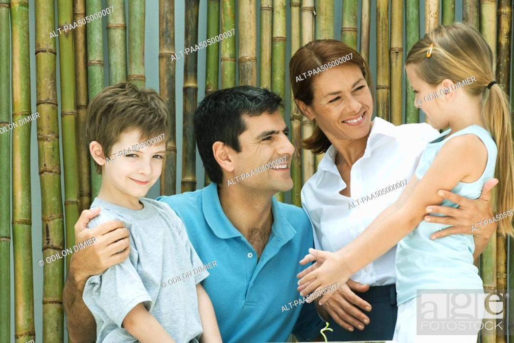 Stock Photo: Family smiling at each other in front of bamboo, group portrait, boy looking at camera.
