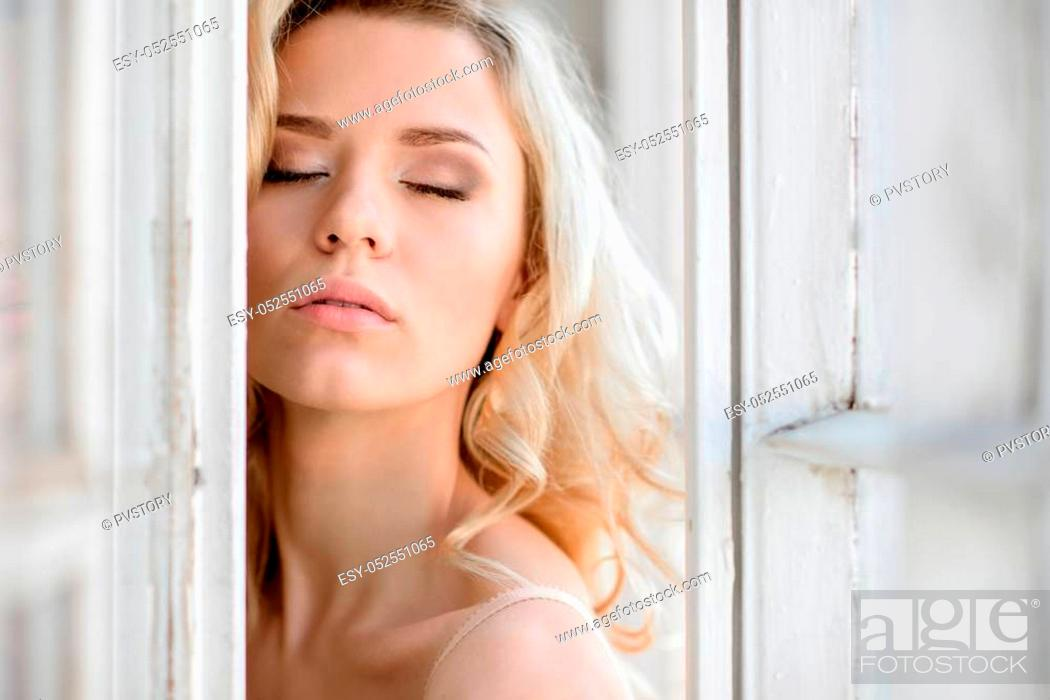Stock Photo: Female portrait of cute lady indoors. Close up beautiful sexy model girl in elegant pose. Closeup beauty blonde woman with hairstyle.