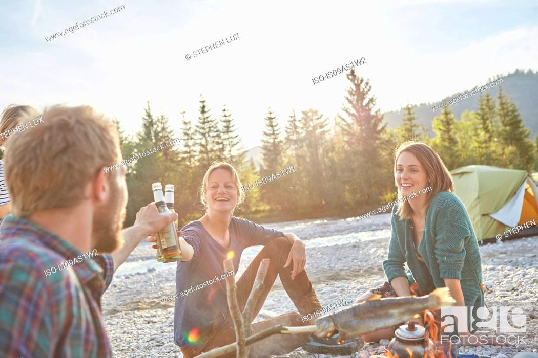 Stock Photo: Adults sitting around campfire making a toast with beer bottles.