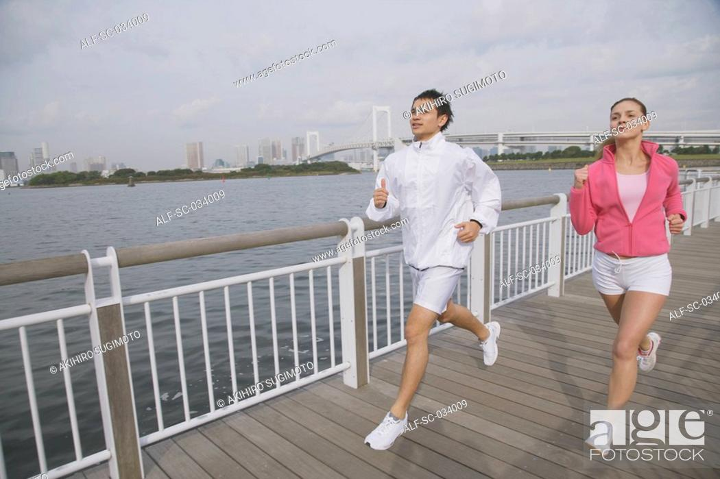 Stock Photo: Young couple jogging on bridge.
