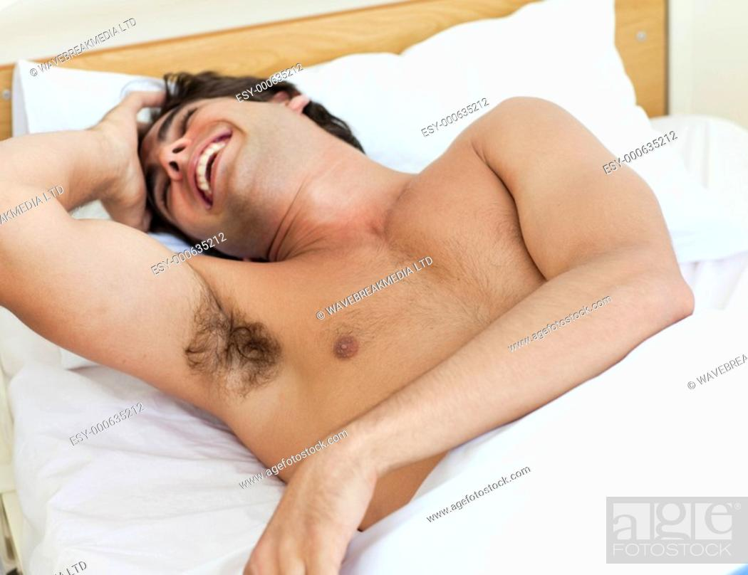 Stock Photo: Portrait of a barechested man laughing on a bed.