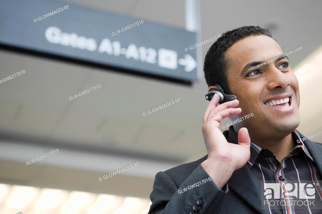 Stock Photo: Close-up of a businessman laughing in a hands free device at an airport.