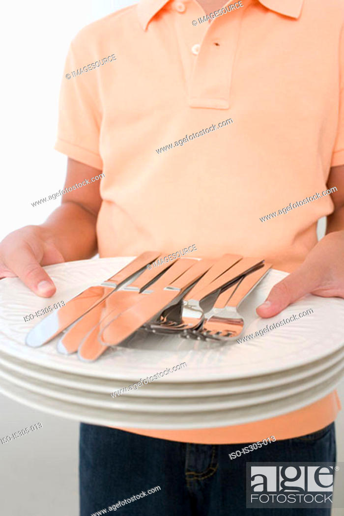 Stock Photo: Boy holding plates and cutlery.