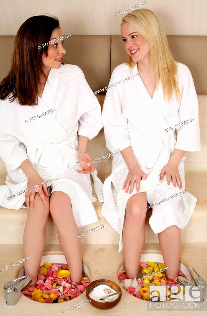 Stock Photo: Two young women enjoying a foot bath with rose petals.