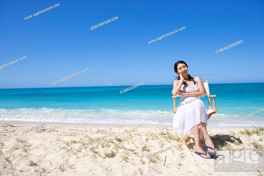 Stock Photo: A young woman sitting on a chair at beach.