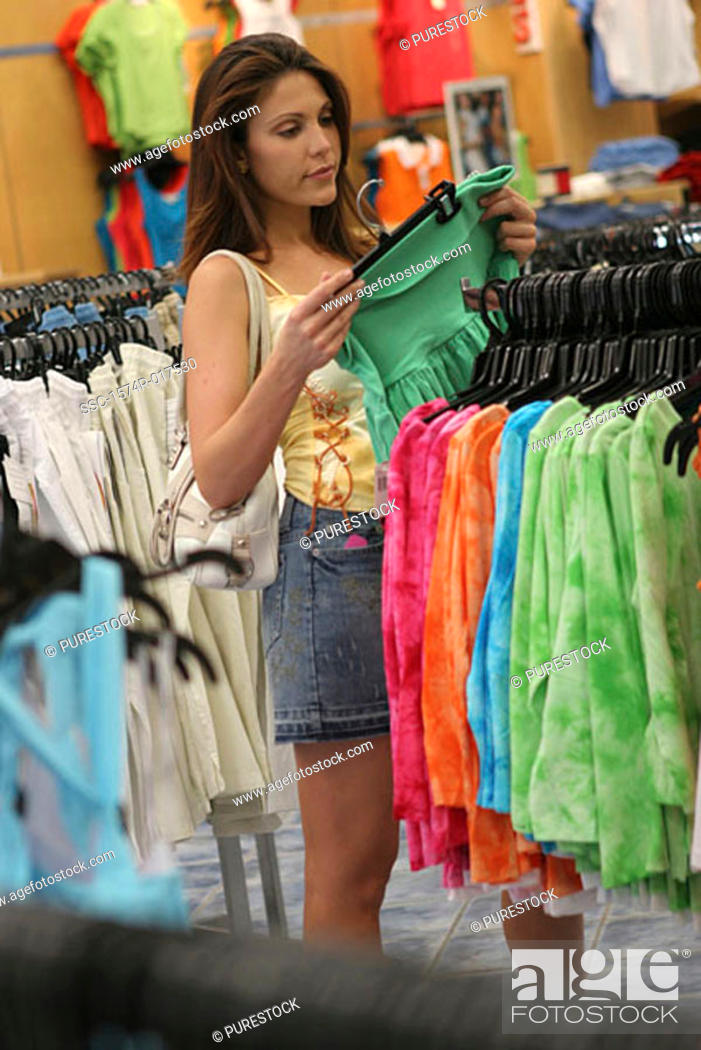 Stock Photo: Side profile of a young woman selecting clothes in a clothing store.