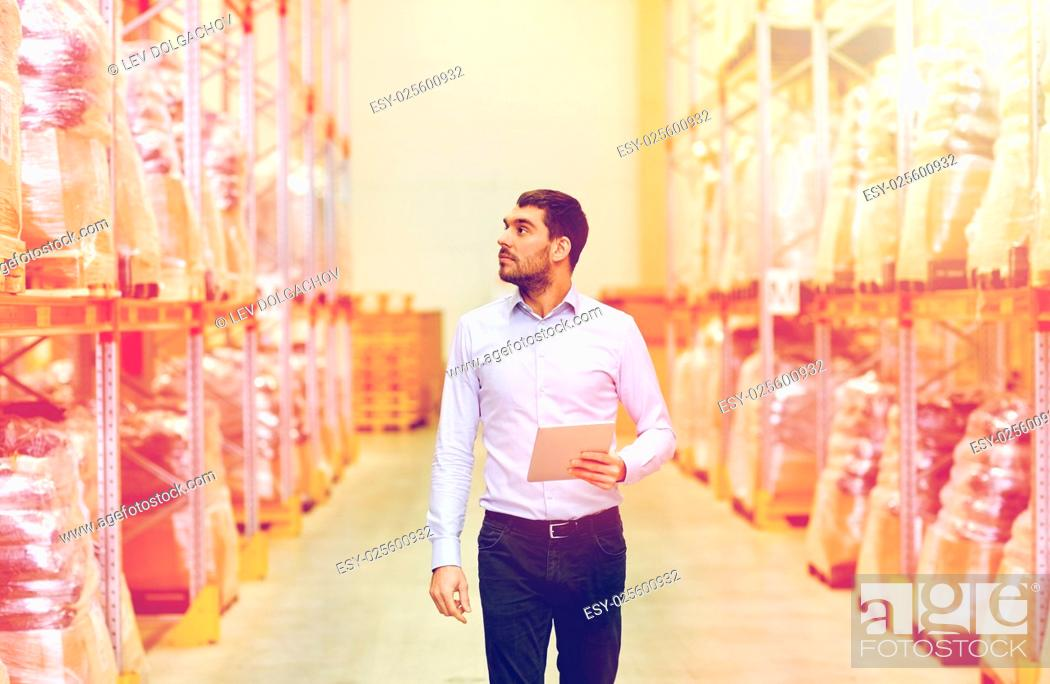 Stock Photo: wholesale, logistic, business, export and people concept - man or manager with tablet pc computer checking goods at warehouse.