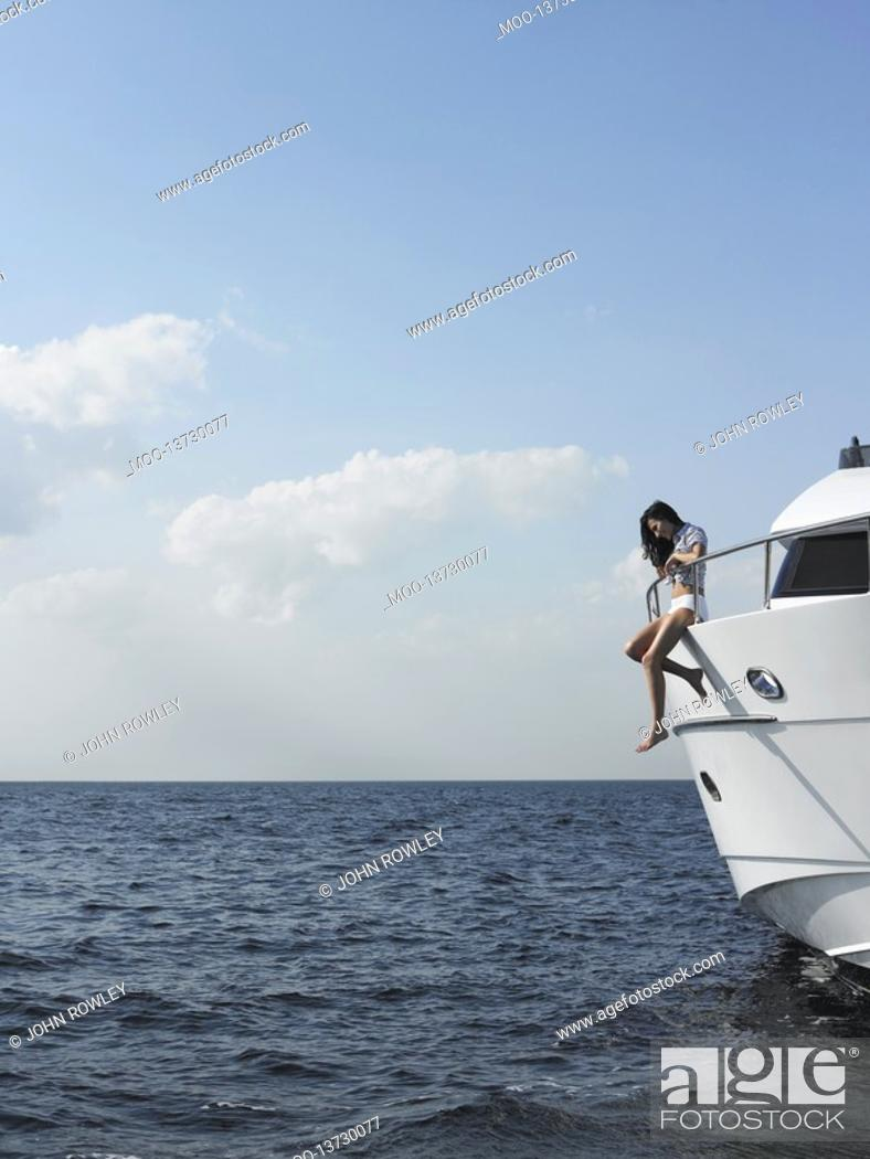 Stock Photo: Young woman sitting at edge of yacht with legs dangling overboard side view.