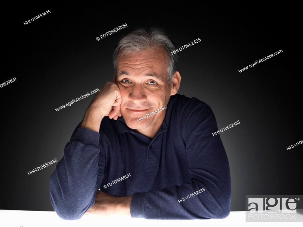 Stock Photo: Mature man leaning against his hand (portrait).