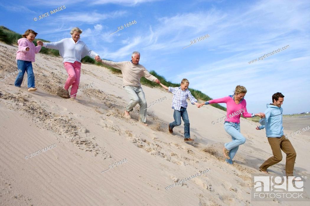 Stock Photo: Multi-generation family running down on beach.