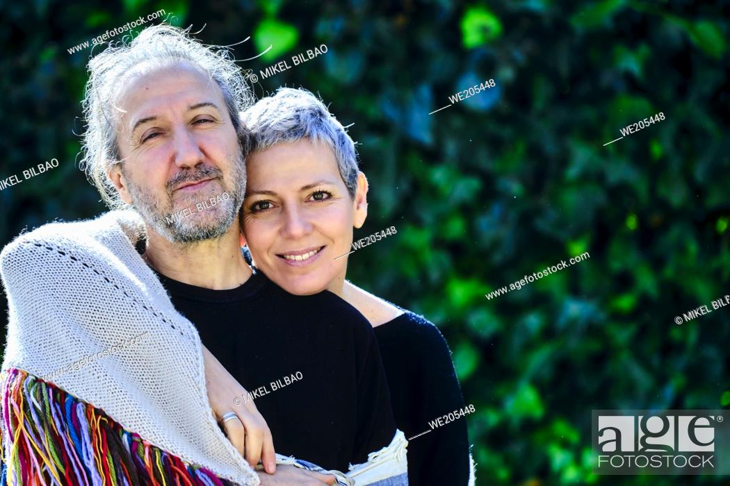 Imagen: Mature and happy caucasian couple posing hugging outdoor in a garden with a leaves background.