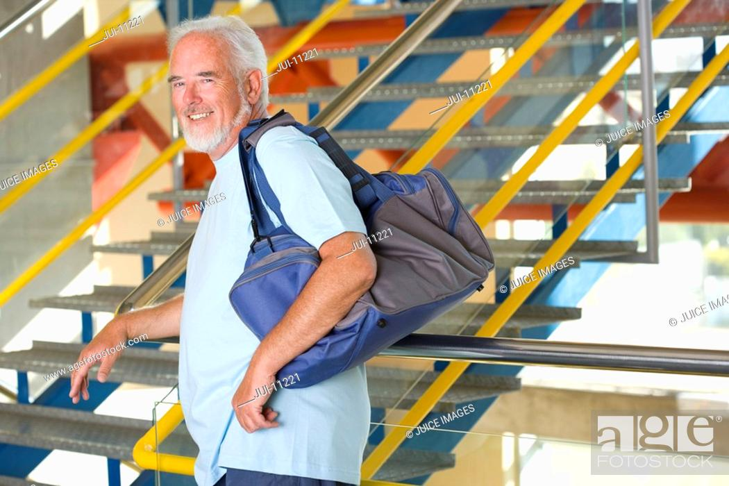 Stock Photo: Senior man with gym bag by stairs, portrait, side view.