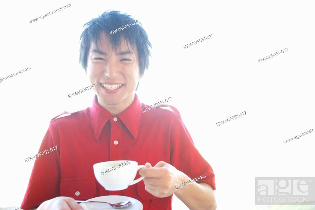 Stock Photo: Young man holding tea cup, portrait.