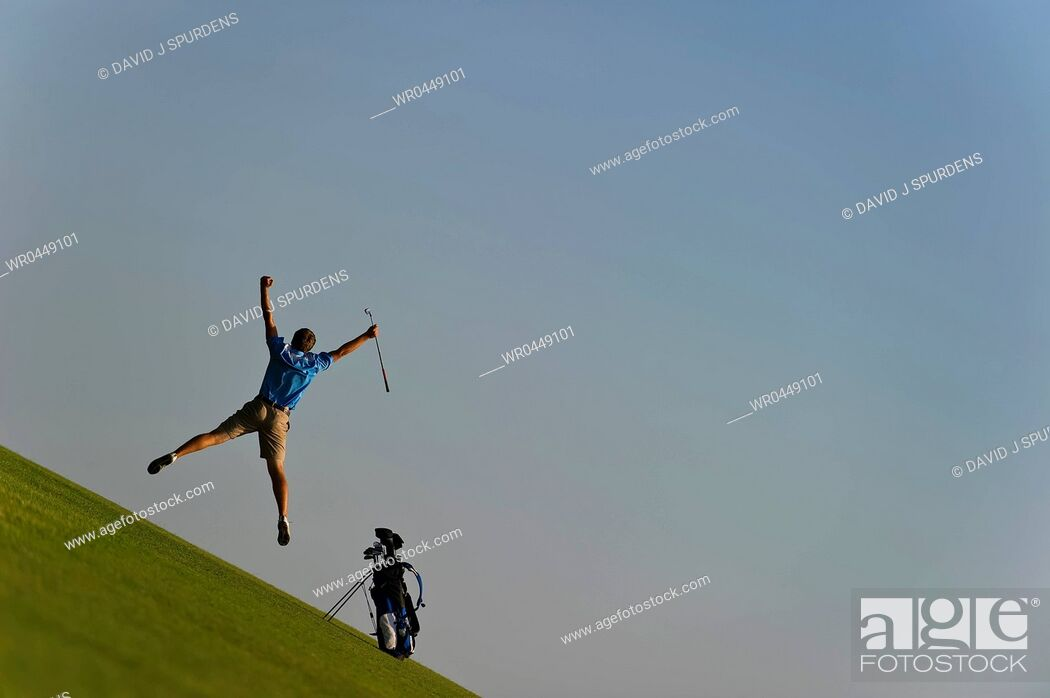 Stock Photo: A golfer leaps into the air in celebration.