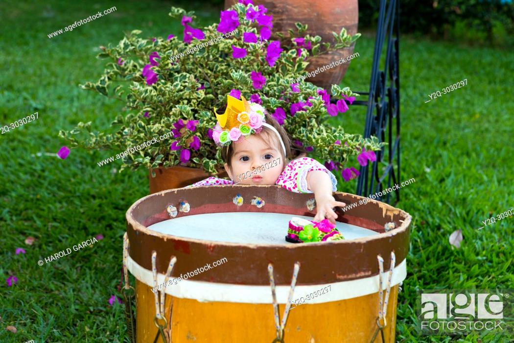 Imagen: curious girl in traditional dance dress behind a drum trying to get her toy.