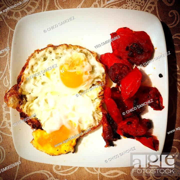 Stock Photo: Two fried eggs and guilled tomatoes for breakfast in Prado del Rey, Sierra de Grazalema, Andalusia, Spain.