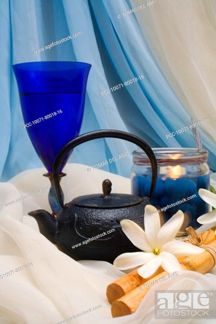 Stock Photo: Spa elements, candle, flowers, kettle and glass nestled upon flowing cloth.