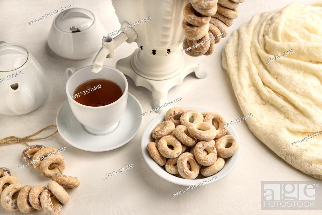 Imagen: a samovar with bagels and hot tea on the white tablecloth.