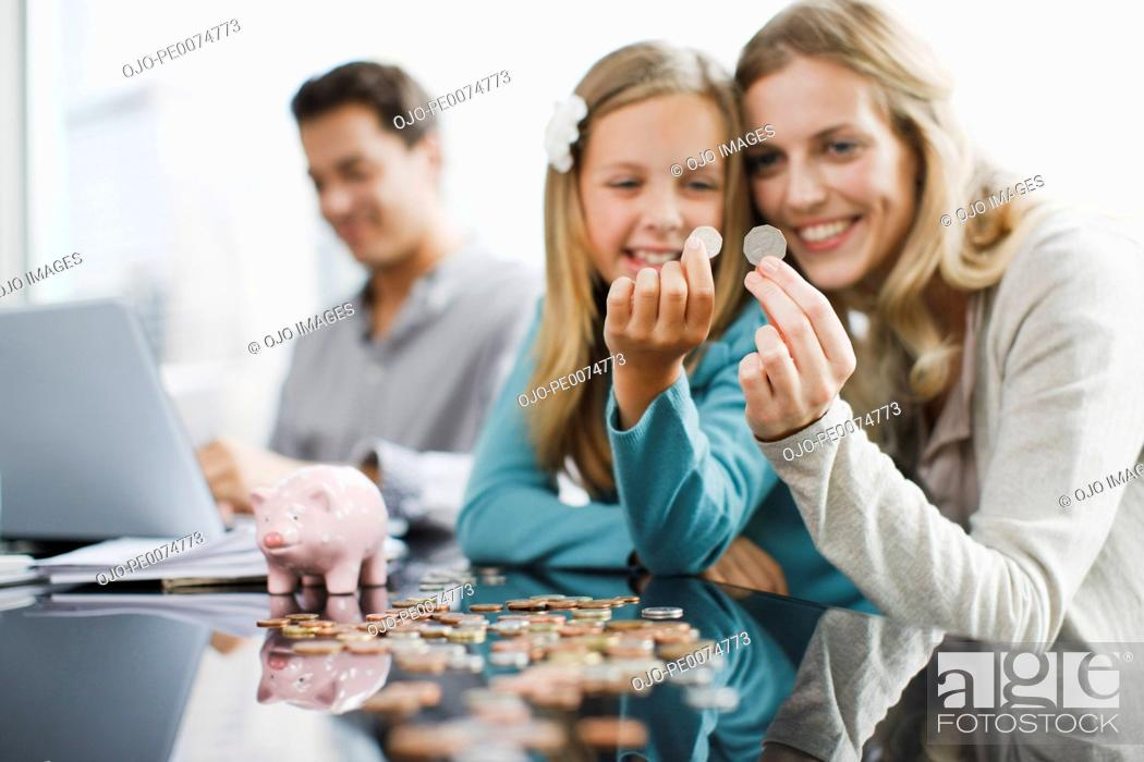 Stock Photo: Mother and daughter comparing coins.