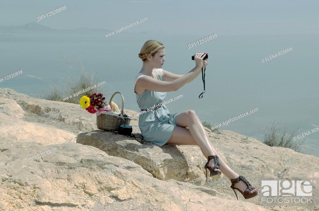 Stock Photo: A young woman in stiletto heels sits on a rock with a picnic basket using binoculars on the coast; Spain.