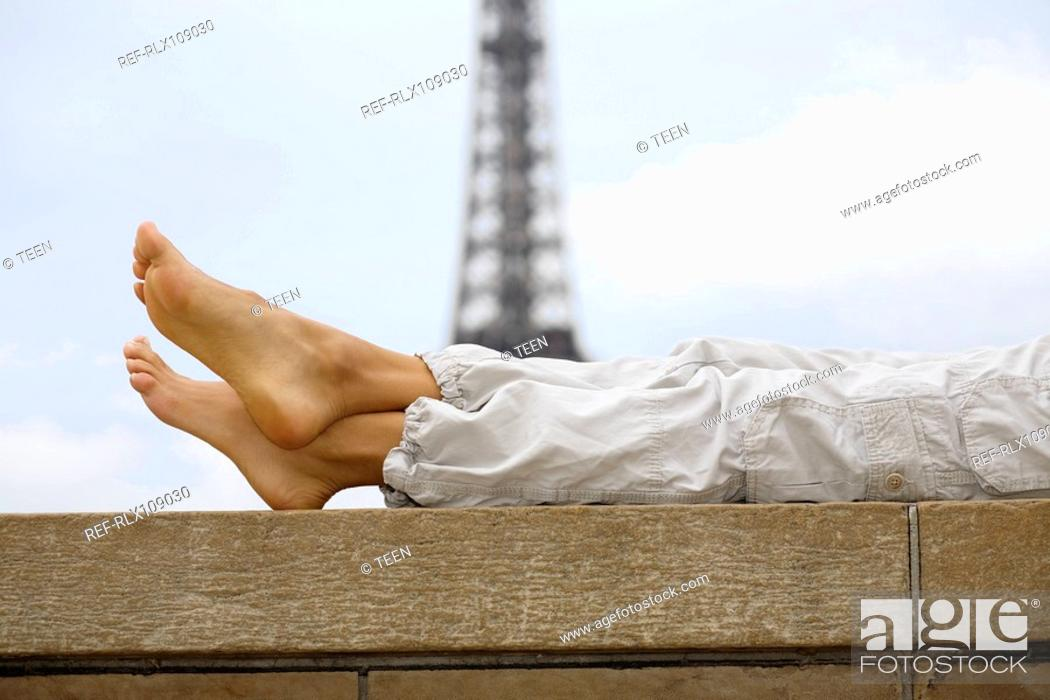 Stock Photo: Close up of woman's legs with Eiffel tower in background, Paris, France.