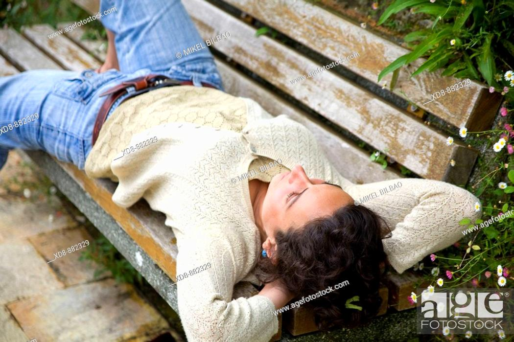 Stock Photo: Young woman portrait resting on a bench.