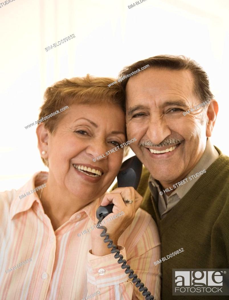 Stock Photo: Senior Hispanic couple talking on telephone.