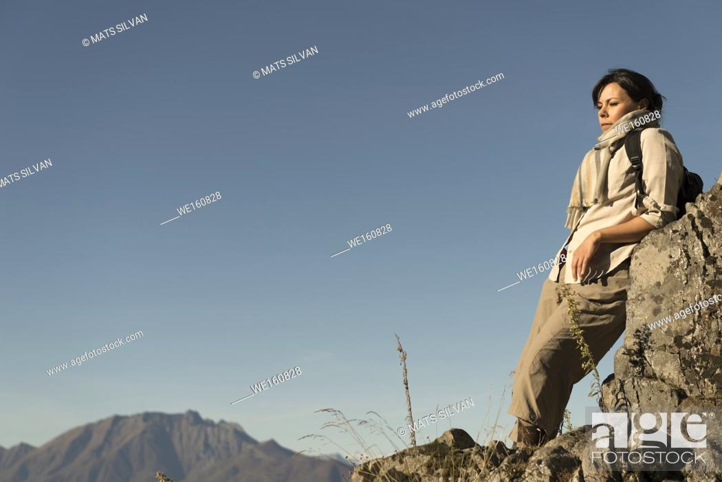 Stock Photo: Woman Relax on a Mountain Top with Alpine Lake Maggiore in Background in Ticino, Switzerland.