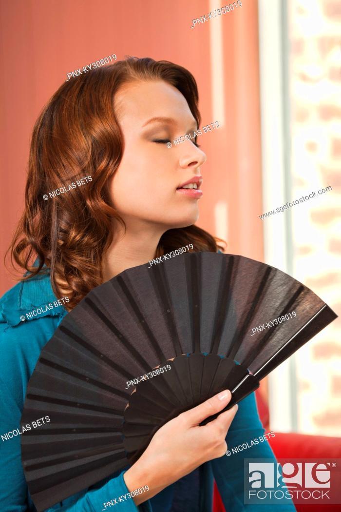 Stock Photo: Young woman using fan.