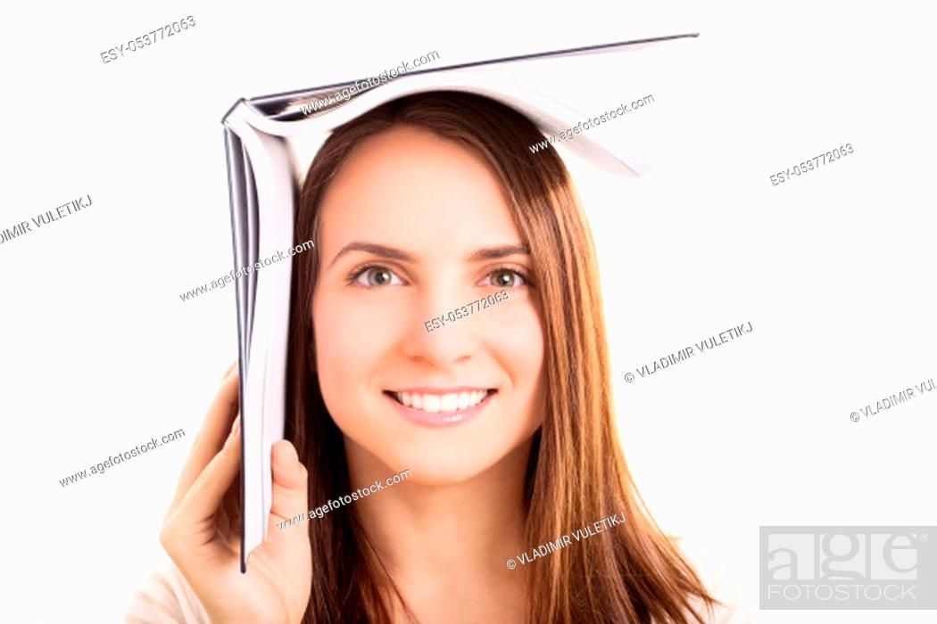 Stock Photo: Young girl holding a book on top of her head, isolated on white background. I'm hiding from the exams.
