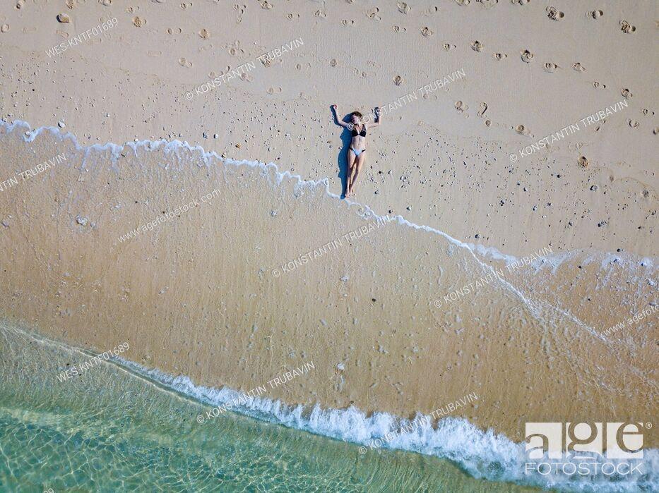 Stock Photo: Indonesia, Bali, Melasti, Aerial view of Karma Kandara beach, woman lying on beach.