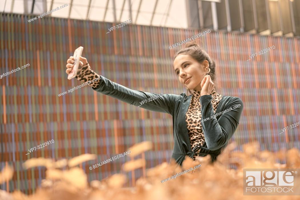 Stock Photo: woman using smartphone, taking selfie, video conversation.