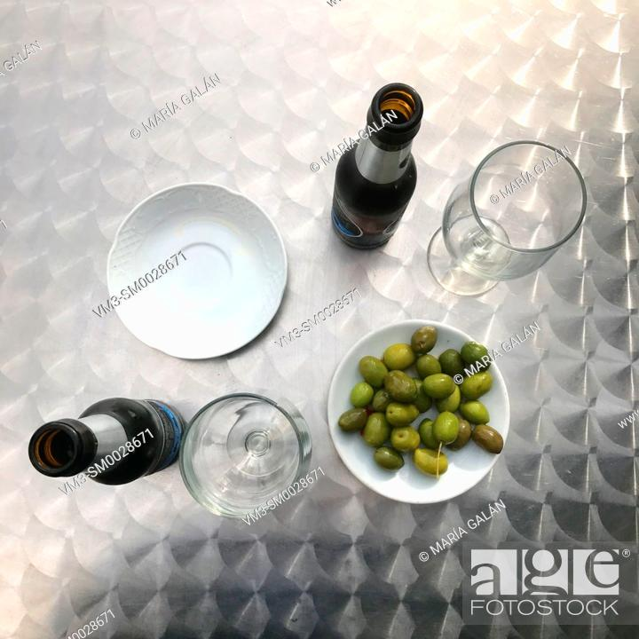 Stock Photo: Two bottles of beer with olive greens in a terrace, view from above.