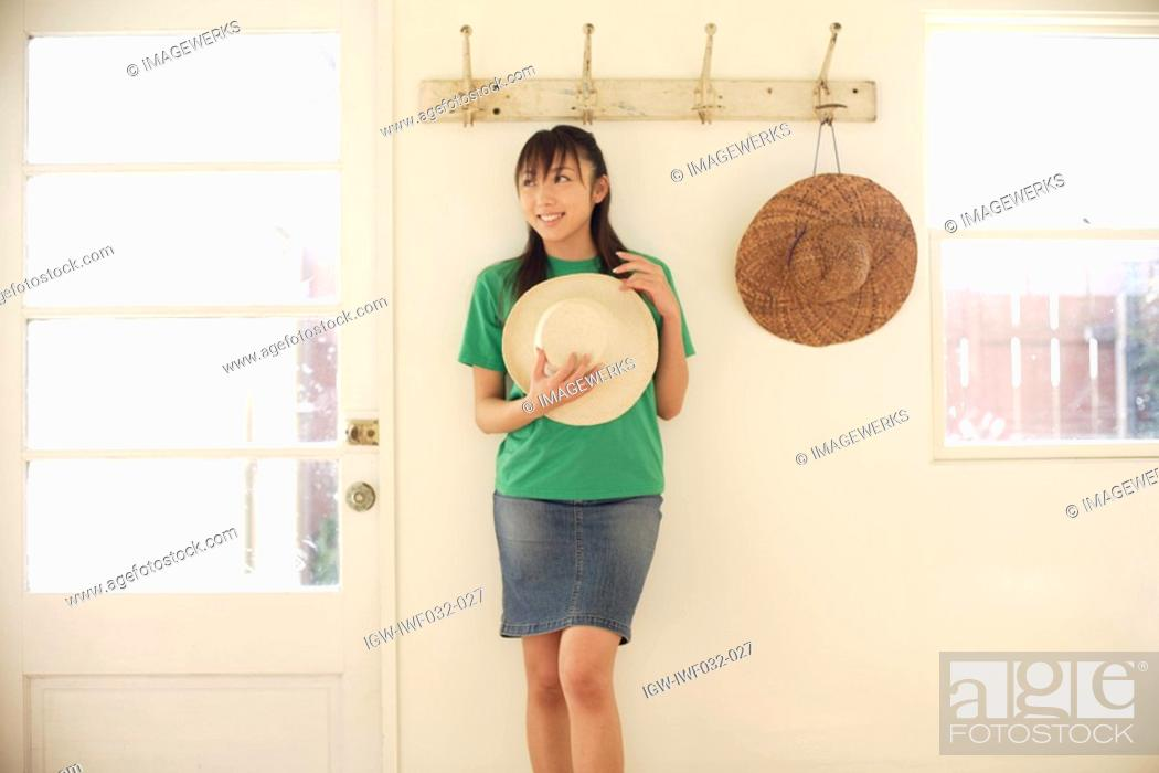 Stock Photo: View of a smiling woman holding hat.