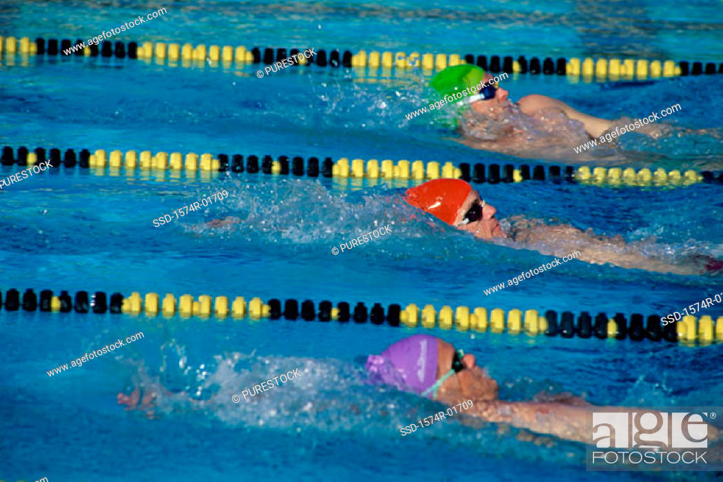 Stock Photo: Three male swimmers in a race.