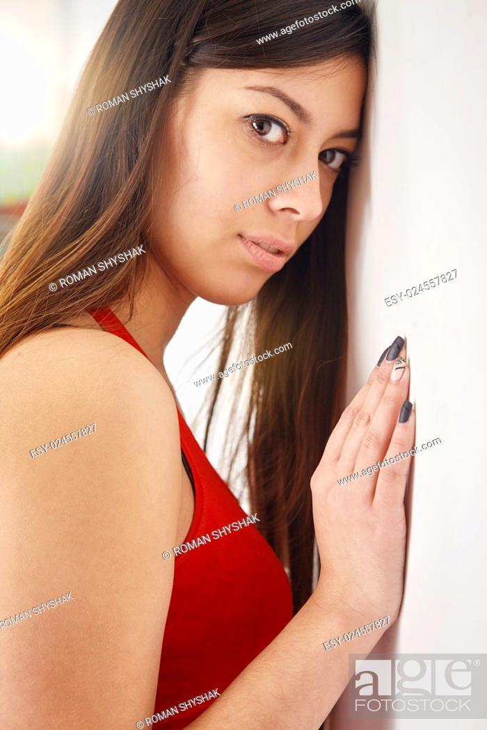 Stock Photo: Young woman leaning against the stone wall, looking at the camera.