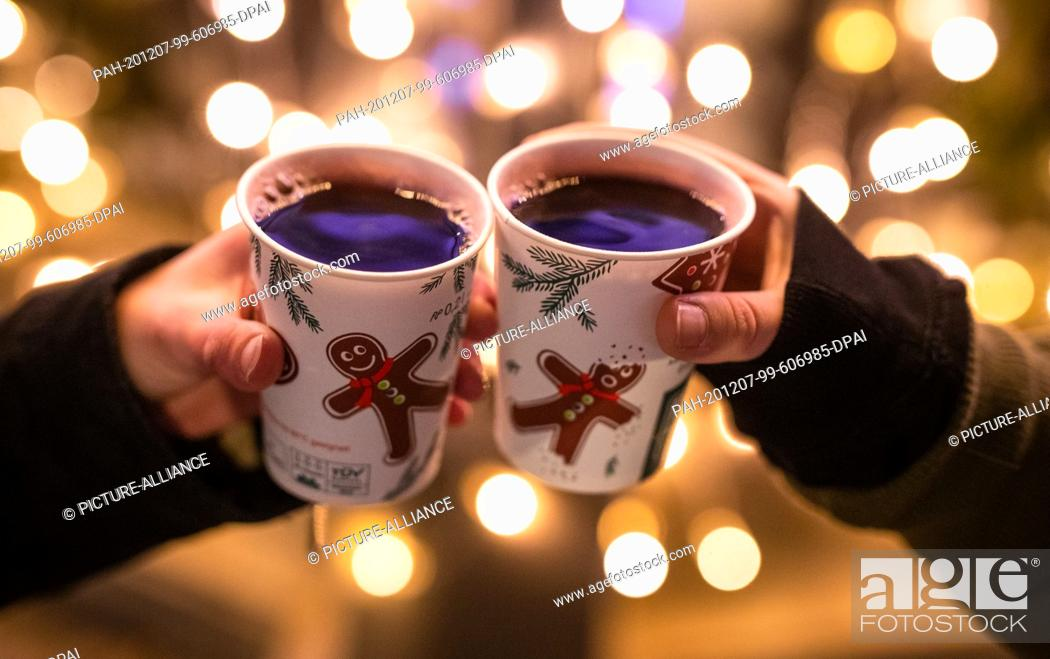 Stock Photo: 07 December 2020, Baden-Wuerttemberg, Stuttgart: Two women toast at Schlossplatz during the Corona pandemic with cups filled with mulled wine.