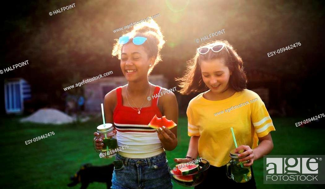 Imagen: Cheerful young teenager girls friends outdoors in garden, carrying watermelon.