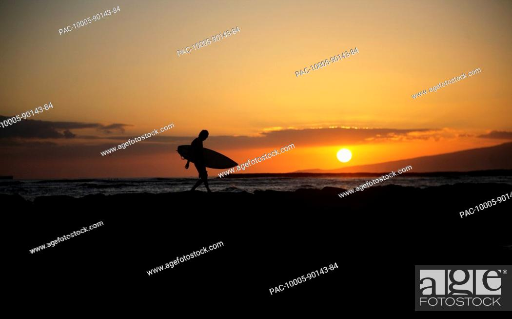 Stock Photo: Hawaii, Oahu, Waikiki, Silhouette of a surfer walking on a rock wall at sunset.