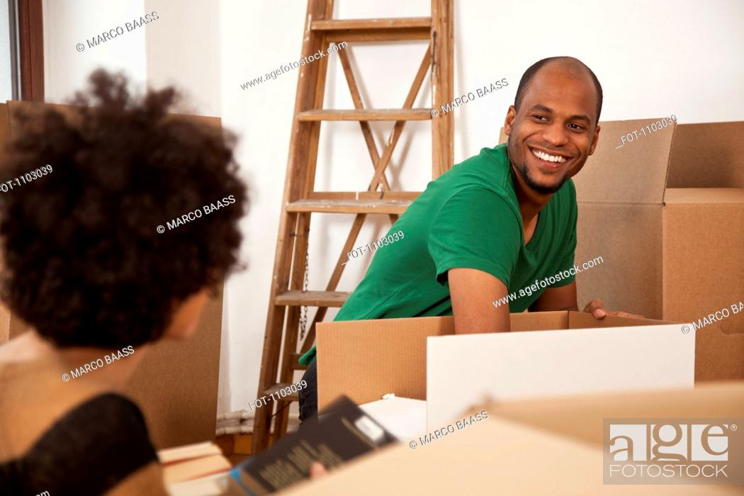 Stock Photo: A cheerful couple packing moving boxes, focus on man.