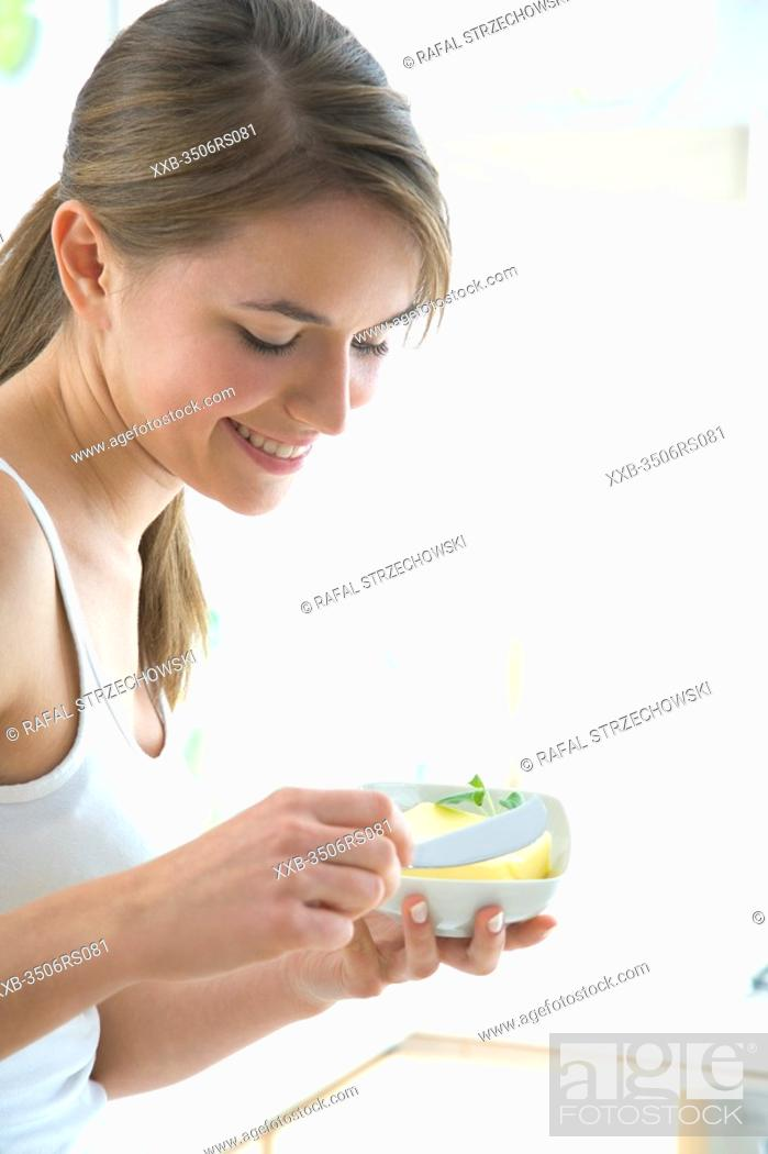 Stock Photo: young woman holding butter.