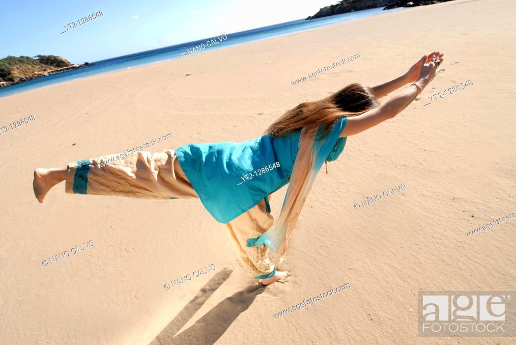Stock Photo: Yoga teacher and artist Lena Tancredi, doing yoga on a peaceful beach of Ibiza, Spain.