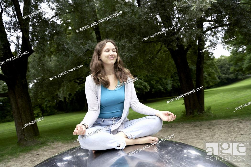 Stock Photo: Woman doing yoga in park. Munich, Germany.