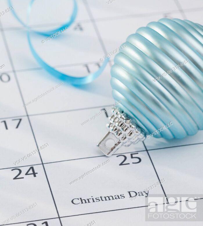 Stock Photo: USA, Illinois, Metamora, Christmas bulb laying on calendar.