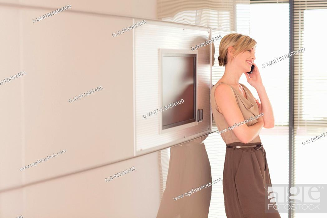 Stock Photo: Businesswoman talking on cell phone in conference room.
